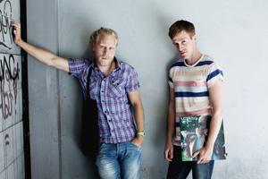 Två unga män i jeans vid en grå vägg, en håller en LP-skiva under armen.
