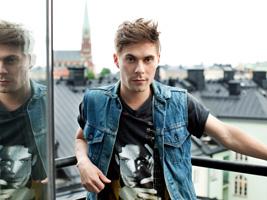 Ung kille med jeansväst på balkong med stadsvy i bakgrunden