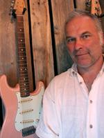 Man med vit skjorta och rosa elgitarr mot trävägg i bakgrunden.